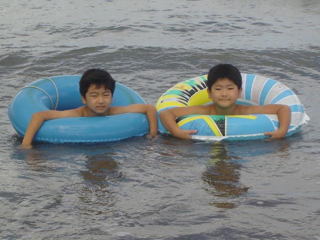 浮き輪をつけて海水浴する子供達